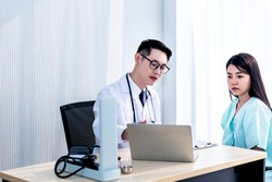 Asian man doctor is using computer To explain the symptoms And treatment procedures Let the woman patients know, with white background, o health care and health insurance concept.