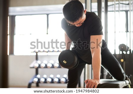 Asian man doing one-handed bent-over row in a training gym Stock fotó ©