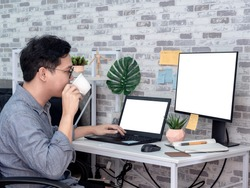 Asian man drinking coffee and working with laptop computer with white blank screen and watching another monitor in his room, condominium. Work at home and business online concept.