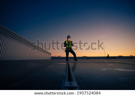 Asian man engineer service check installation solar cell on the roof of factory on the morning. Silhouette technician with solar cell on the roof of factory under morning sky. Technology solar cell.