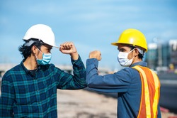 Asian man Engineer shake hand not touch new normal style,Two Engineer a wearing face mask protect corona virus PM2.5 on site construction