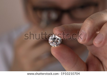 Asian man expert buyer with glasses evaluates polished diamond trough magnifying glass close up.  Foto stock ©