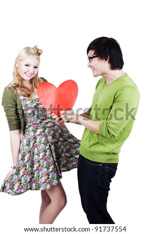 Asian man gives a bug heart cutout to his caucasian girlfriend. Isolated on white