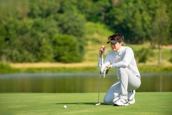 Asian man golfer  sitting  on fairway aiming ball to  golf hold at golf course  , Sport healthy holiday lifestyle  Concept , Banner for text