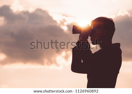 Asian man Hand Holding Binoculars / looking / watching using Binoculars with copyspace,Concept of The pursuit of profitable business in the future.