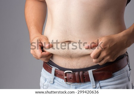 asian man hand holding excessive belly fat