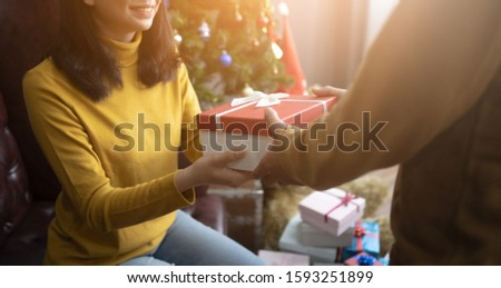 Asian man handsome with gift box surprise for girlfriend.Merry Christmas and happy new year.happy couple surprising each other with Christmas presents.