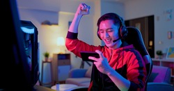 asian man have live stream and win mobile game on the smartphone with raising arm at home