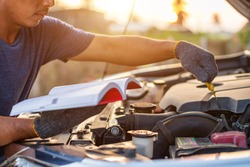 Asian man holding and reading the car user manual or user instruction to checking or fixing engine of modern car. Car maintenance or service before driving concept