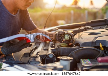 Asian man holding and reading the car user manual or user instruction to checking or fixing engine of modern car. Car maintenance or service before driving concept ストックフォト ©