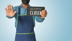 Asian man holding notice board sorry we are closed sign hanging a restaurant, store, office or other, business open back to new normal after coronavirus, covid-19. with clipping path