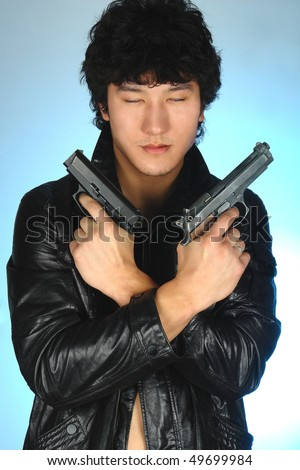 asian man holding two guns in hands