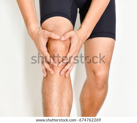 asian man holds on to the knee, the pain in the knee on white background