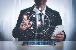 Asian man in a suit is sitting at a desk with his left hand holding a mobile phone. His right hand pointing at a hologram showing business icons in hitech circle . Black background blur