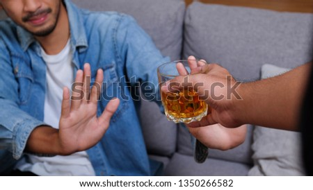 Asian man in blue jean jacket refuses to drink a alcohol by stopping hand sign. Male alcoholism concept. Treatment of alcohol addiction. Quit booze and alcoholism