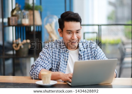 Asian man in blue shirt  using laptop and drinking coffee in coffee shop cafe working online freelance business