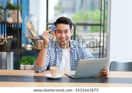 Asian man in blue shirt  using laptop for shopping online with credit card and  drinking coffee in coffee shop cafe working online freelance business
