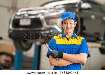 Asian man in car service, repair, maintenance and people concept, happy smiling auto mechanic man or smith with clipboard at workshop