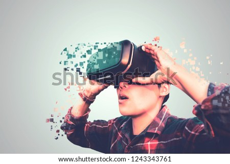 Asian man in tartan shirt wearing glasses of glasses of virtual reality dissolving into pixels on gray background Future technology Concept