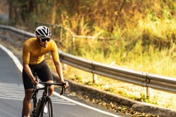 Asian man in yellow cycling jersey rinding on road bike up high on hill,  In a good weather morning, under morning sunlight.