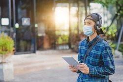 Asian man listening music head phone wearing face mask outdoor lifestyle new normal