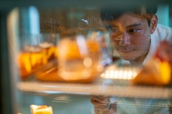 Asian man looking and choosing variation of delicious cake in bakery showcase fridge at cafe. Male customer buying tasty sweet dessert at coffee shop. Small business restaurant food and drink concept