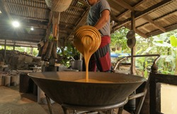 Asian man making boiled palm coconut sugar or cane production process, raw material, Amphawa, Thailand. Traditional culture lifestyle. Local sweet food.