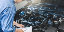Asian Man mechanic inspection writing note on clipboard.Blue car for service maintenance insurance with car engine.for transport automobile automotive image.