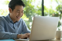 Asian man on blue shirt smiling while using a laptop. Happy face smiling asian black short hair man looking at a laptop with green background. Freelancer working and looking at laptop.