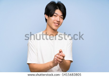 Asian man on isolated blue background applauding #1415683805