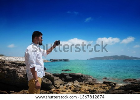 Asian man on the beach making photo on the mobile near blue ocean or blue sea #1367812874