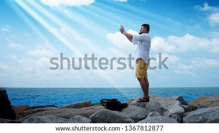 Asian man on the beach making photo on the mobile near blue ocean or blue sea #1367812877