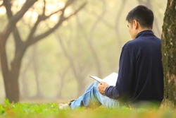 Asian man peacefully reading a book under the tree in the woodland with a ray of morning light for freedom and relaxation pursuit concept