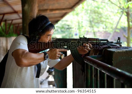 Asian man posting in ready position to shoot an AK-47 rifle.