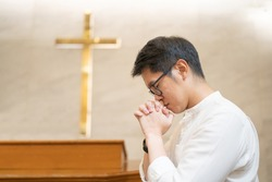 Asian man praying in a worship room in a Christian church.