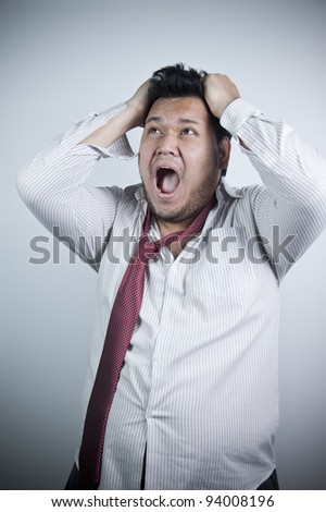 Asian man, pulling his hair, making very stressed expression on his face