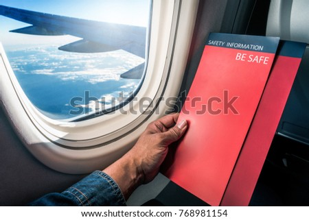 Asian man read flight safety instructions on card board flight. Blank safety instructions on board for passenger and traveler safety.