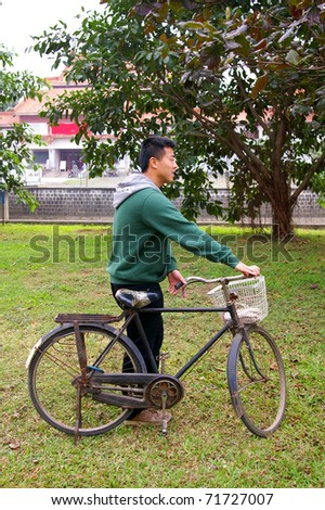 Asian man riding and carrying bicycle