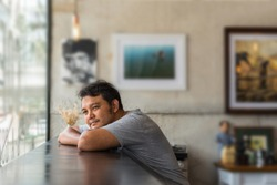 Asian man 40s in gray t-shirt happiness with shy and inlove between waiting something or missing lover in a coffee shop cafe