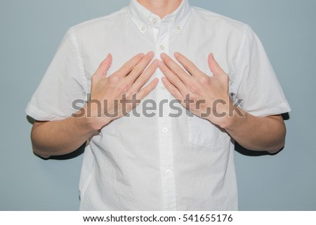 Asian man showing his heartfelt gratitude and thanks clasping his hands to his heart