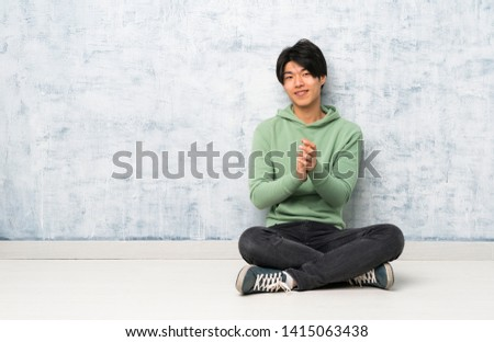 Asian man sitting on the floor applauding after presentation in a conference #1415063438