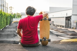 Asian man sitting with surfskate or skate board in pumptrack skate Park when sunrise time over photo blur of pumptrack curve, extream sport, healthy and exercise, fashion in covid19 concept