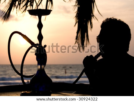 asian man smoking hookah on a beach side restaurant next to the sea in an evening