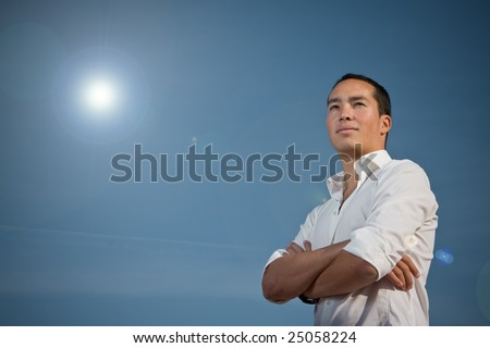 Asian man standing against blue sky with arms folded with sun shining in the background with artistic lens flare. #25058224