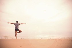 Asian man standing in yoga tree pose on ocean beach at sunset, relax holiday vacation time at tropical beach. Young man with bare foot on sand beach in orange tone.