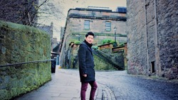 Asian man standing on Cobblestone in alley, Edinburgh, Scotland, United Kingdom
