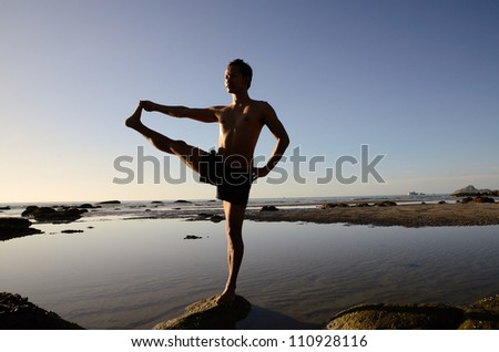 Asian man standing on one leg in yoga pose and one of his hand stretching with another leg.