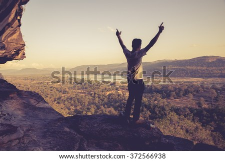 asian man standing with arms...
