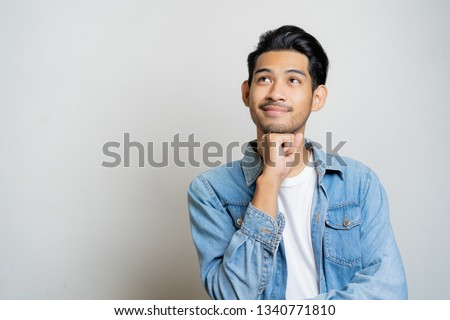 Asian man thinking and smiling.