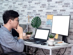 Asian man thinking and working with laptop computer with white blank screen and watching another monitor in his room, condominium. Work at home and business online concept.